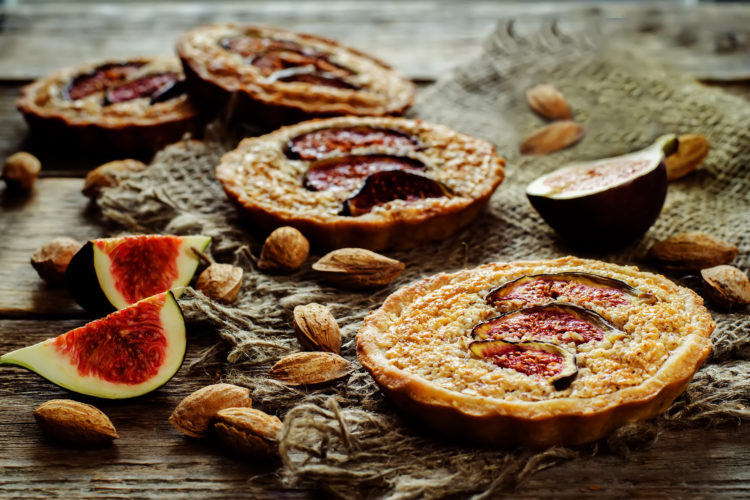 tartlets with Fig and almond cream (Frangipane) on a dark wood background. tinting. selective focus on the middle of the front tartlet